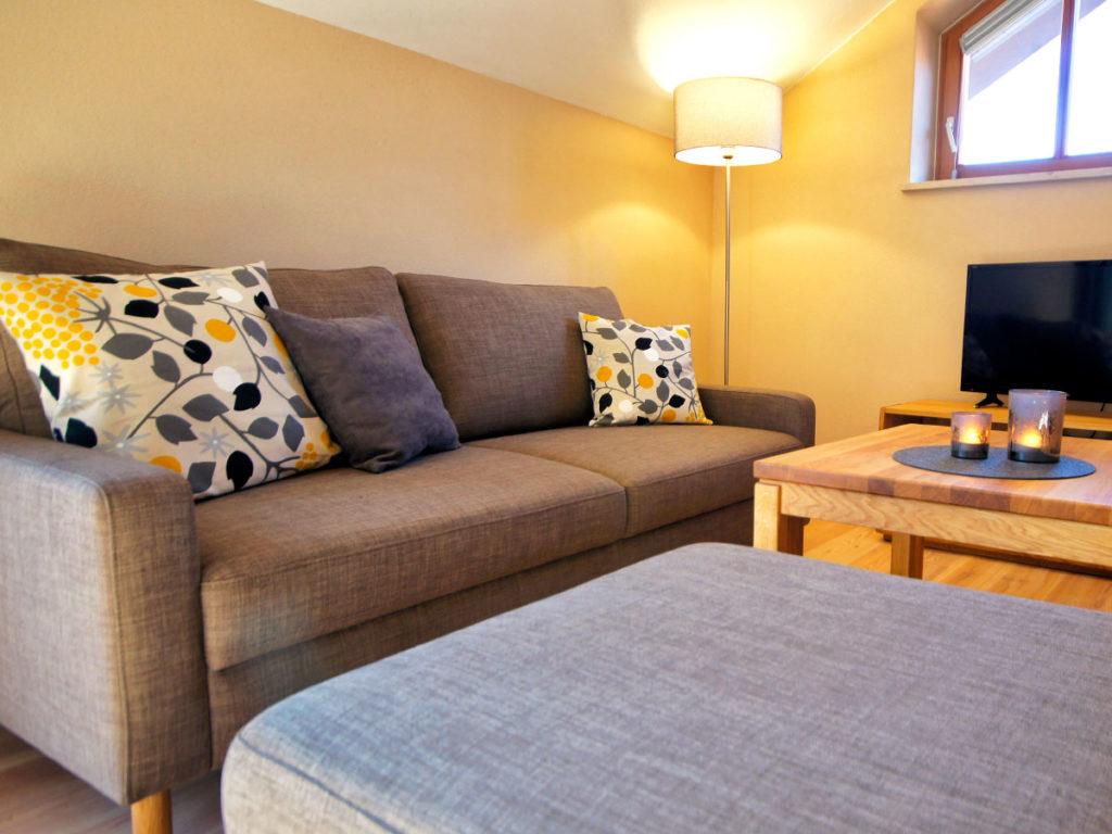 Graues Sofa mit bunten Kissen und Sofatische in der Ferienwohnung Zaungast.