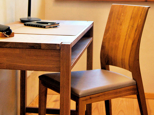Detailansicht eines Schreibtisches mit Stuhl aus Vollholz.