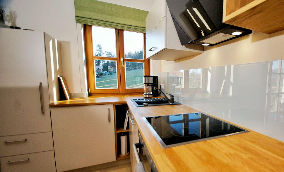 Moderne Küche aus Vollholz mit Blick aus dem Fenster ins Grüne in der Ferienwohnung Augenweide.