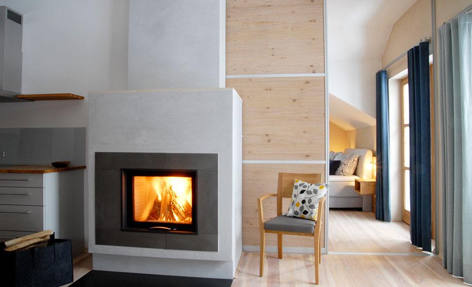 Ein brennender Kamin und eine Schiebetür teilen den Wohn- und Schlafbereich in der Ferinwohnung Zaungast.