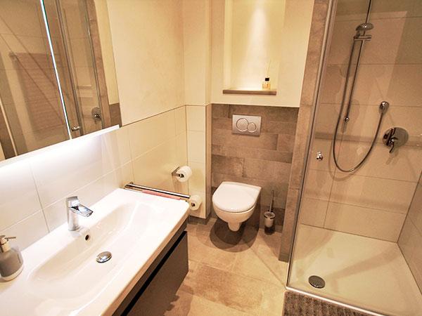 Das Badezimmer in der Ferienwohnung Zaugast besticht durch natürliche und hochwertige Materialien wie beige Steinfliesen und weiße Keramik.