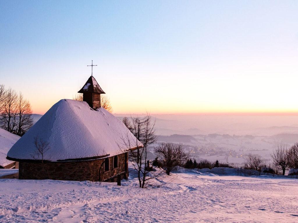 Eine kleine Kapelle im winterlichen Sonnenuntergang.