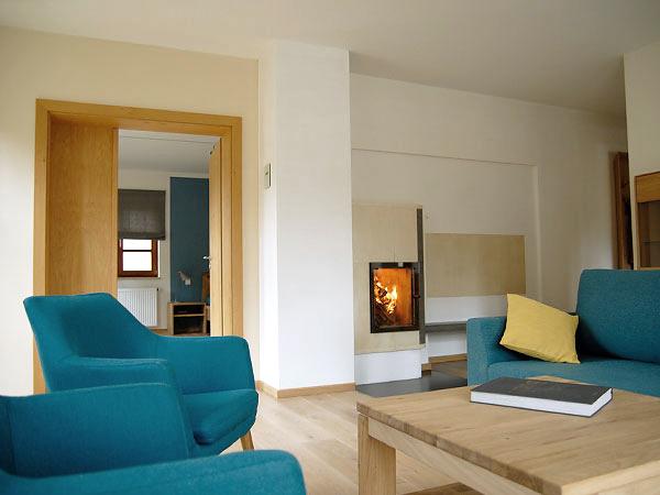 Wohnzimmer mit blauen Sesseln in der Ferienwohnung Naturkino.